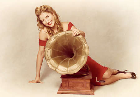 phonograph: Attractive retro 60s pin up girl smiling beside vintage record phonograph music player holding large brass horn in a depiction of old classic audio Stock Photo