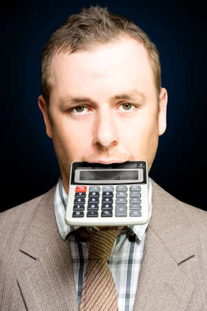 financial controller: A studious looking young accountant grips a desk calculator between his teeth conceptual of number crunching and financial analysis Stock Photo