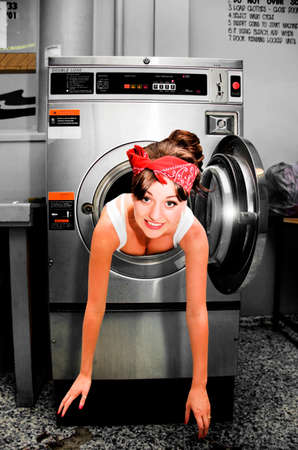 coming out: House Work Help Sees A Funny And Humorous Home Cleaning Woman Caught Stuck and Trapped Inside A Clothes Dryer When Doing House Choirs Stock Photo