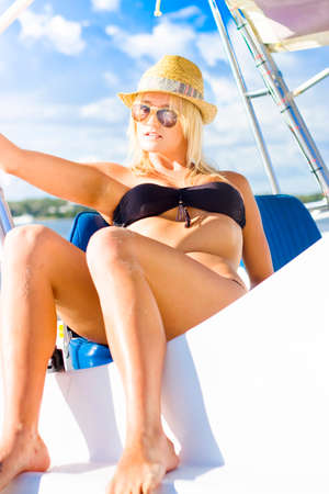 sprawled: Blonde Female Boat Skipper Sitting Unwinding Resting And Tanning In The Summer Sun While On A Boating Holiday In A Scene Of Beauty And Holidays Stock Photo