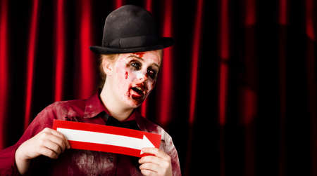 thespian: Zombie theatre show performer standing in front of stage curtains holding arrow in a Halloween horror show concept Stock Photo