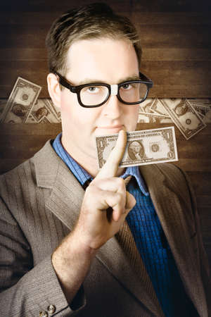 concealment: Banking business man standing in front of a concealment of stashed money holding American one dollar note in a depiction of personal wealth and finance Stock Photo
