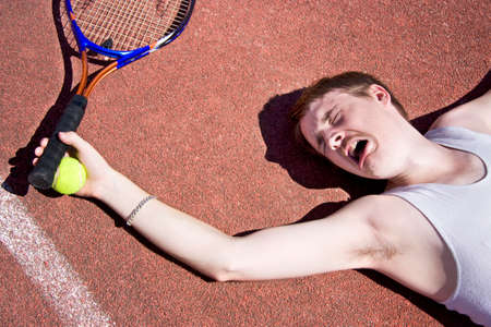 injured person: Clay Court Tennis Player Cries Out For Medical Attention With An Injured Elbow Stock Photo