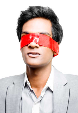 abduct: A young Asian business man has his eyes taped shut with a band of red tape conceptual of either Blinded by red tape due to unnecessary bureacracy or Held to ransom by a terrorist cell for funding