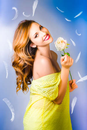 tryst: Smiling woman holding a white rose with feathers on the blue background