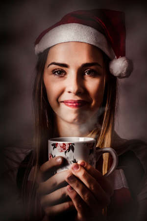 indulging: Dark holiday photo of a beautiful friendly girl indulging in a warm christmas hot cocoa drink. Holiday cafe