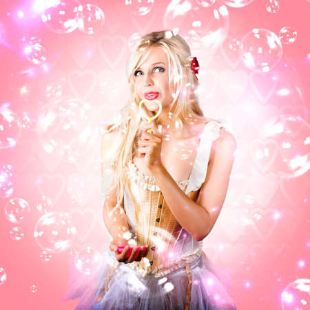 pink bubbles: Attractive Blond Female Cupid Blowing Kisses Through A Heart Shaped Bubble Blower In A Valentines Day Love Concept On Pink Hearts Background