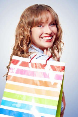 gleeful: Happy female shopper with a gleeful smile carrying a carrier bag with her days haul of bargains from the shopping mall Stock Photo