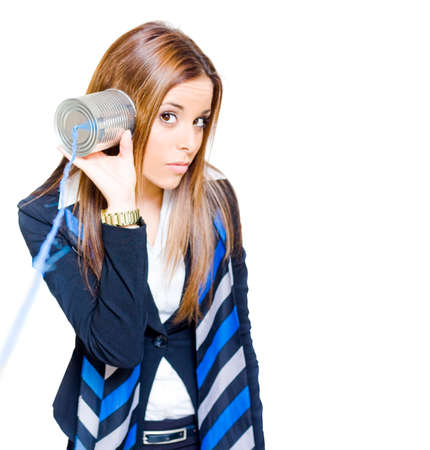 tin can telephone: Business Technology And Communication Concept With An Attractive Brunette Business Woman Listening To A Tin Can Telephone, Isolated On White Background Stock Photo