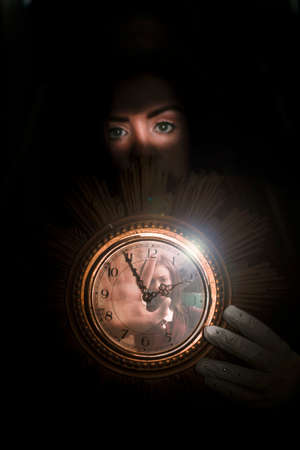 timepiece: Clock Held By Young Woman Shadowed In Black With Another Woman Stuck Inside The Glass Face Of The Timepiece In A Lost In Time Concept