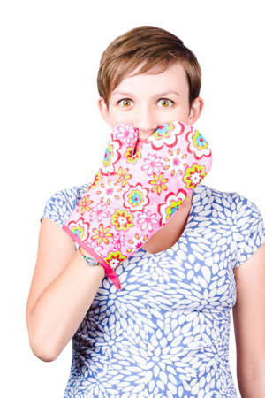concealing: Mischievous young housewife with oven glove held to face with expression of shock. Baking mistake, isolated on white