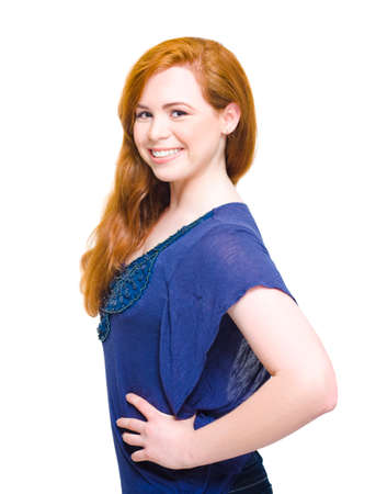 demure: Studio Picture Of A Fresh Faced Beautiful Woman With Auburn Hair Wearing Hippy Clothing Smiling Side-On With Hands On Hips, Over White Background