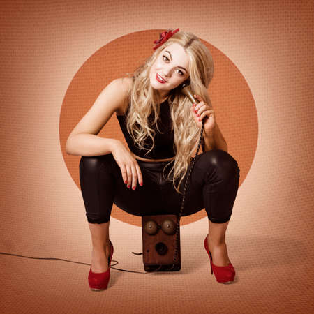 telephone box: Vintage portrait of a smiling blond pin up girl talking on top of retro box telephone wearing red high heel shoes. Good old fashion call Stock Photo