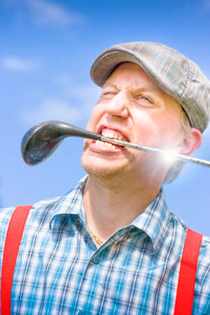 tee off: Crazy Golfer Man Smiles With A Golf Stick In His Mouth While Looking To The Distance After A Tee Off In A Playful Sporting Golfing Mad Concept