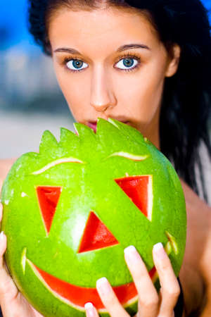 mesmerising: Beautiful Young Female With Black Hair With Expression Of Surprise Holding A Watermelon With Carved Smiling Face With Beach Background