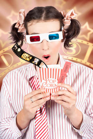 reacting: Fun Image Of A Young Woman In Pigtails Watching A 3D Movie At Cinema With Stereo Glasses Clutching A Classic Box Of Popcorn While Reacting In Amazement To The Three Dimensional Effects