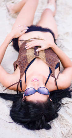 beach babe: Beautiful Beach Babe Laying In The Sand Wearing Bikini And Sunglasses Looking Up At The Sky With Expression Of Peace And Serenity