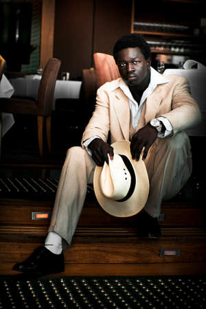 goodlooking: Goodlooking African Male Fashion Model Striking A Pose In A White Suit With Matching Panama Hat While Sitting On A Step Inside A Fine Dining Restaurant