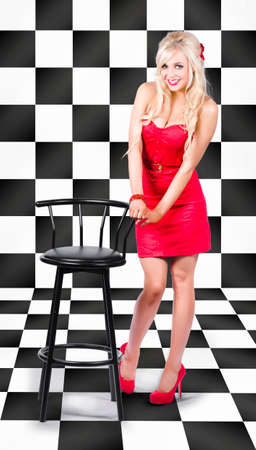 pin up model: 1950s retro pin up model posing with hand to black barstool inside old fashioned checkered cafe