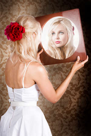 olden day: Indoor portrait of a dreamy blond vintage lady looking at mirror reflection