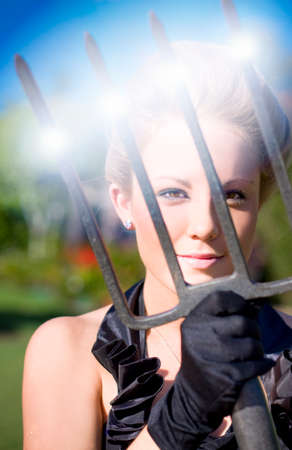 prongs: Portrait Of Glamorous Young Woman With Sunlight Reflecting On Pitchfork In Garden