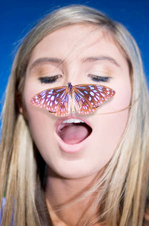 landing light: Nature Connection Concept Showing A Head Shot Of An Attractive Blond Woman With A Butterfly On Her Nose Stock Photo