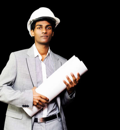 asian architect: Stylish young Asian architect, engineer or contractor wearing a hard hat and holding a rolled set of design blueprints against a black studio background Stock Photo
