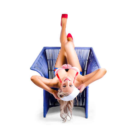 position: Beautiful blond american pin-up woman in red and white top upside down in purple colored wickerwork chair isolated on white background Stock Photo
