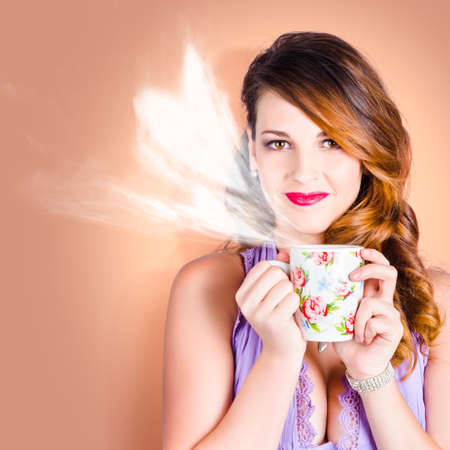 wafting: Adorable young brunette woman with stylish hair drinking coffee cup with heart shaped steam. Coffee love Stock Photo