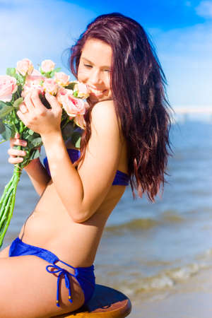 struck: Love Is In Bloom With A Smiling And Happy Love Struck Woman Holding A Gift Bouquet Of Pink Roses When On A Valentines Day Beach Getaway