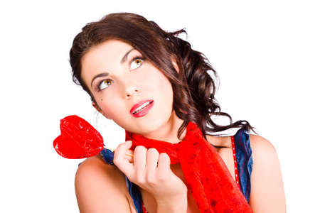 sweet heart: Beautiful pinup girl holding love heart lollypop candy while looking up to blank valentine copyspace. Sweet heart