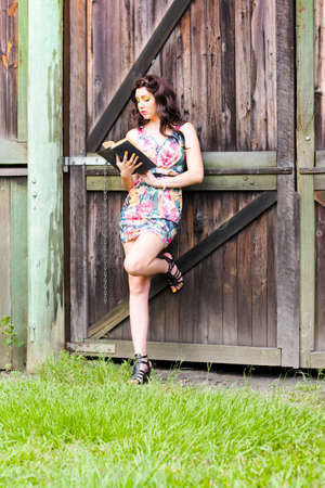 narrative: Story Time Concept Sees An Attractive Woman Reading A Fictional Narrative Novel Against A Wooden Farmyard Shed When On A Holiday Recreation Break Stock Photo