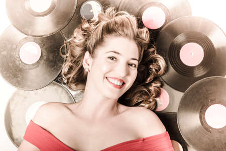 acoustical: Retro pin-up woman with rocking hairstyle laying down some music against a set of 78rpm vintage vinyl records in classic fashion style Stock Photo