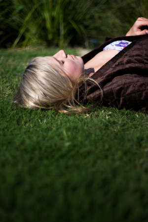 quiet: Woman Sleeping With A Brown Blanket On A Grassy Field While Enjoying The Peace And Quiet Of A Outdoor Nature Reserve