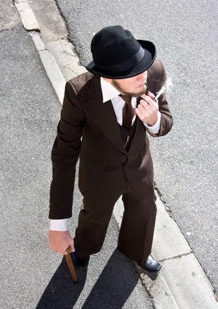 hombre con sombrero: Olden Era Gent camina por la calle con humo de su pipa humeante mientras da un golpe del tabaco del vintage