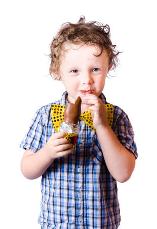chocolaty: Portrait of cute boy in bow tie eating Easter egg, white background Stock Photo