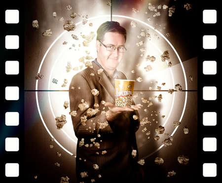 hombre cayendo: Póster de la película concepto de un hombre con el cine de las palomitas con la caída de los granos de pie delante de la pantalla de cine. Bobina de entretenimiento Foto de archivo