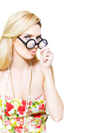 bookish: Attractive young blonde woman wearing round glasses with thick high magnification lenses and a withdrawn shy attitude conceptual of the stereotypical studious nerd lacking in social graces Stock Photo