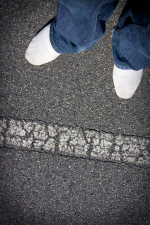 over: White Shoes Of A Pedestrian About To Step Over A Road Line Marking To Get To The Other Side Of The Street