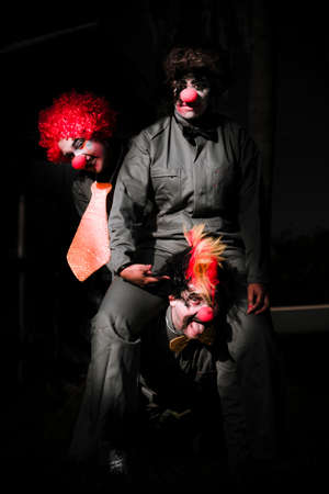 women legs: Three Clowns With Curly Wigs In Playful Position With Dark Background Stock Photo