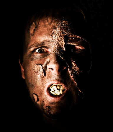 ghoulish: Lurking In The Black Darkness A Festering Zombie Face Peers From The Shadows With Mangled Rotting Teeth And Flaking Skin In A Face Of Death Concept Stock Photo