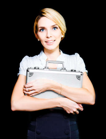 operative: Pretty blonde business woman clutching on tightly to a metal briefcase which she is guarding carefully as it contains classified top secret documents Stock Photo