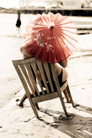 nature beauty: Young Woman Holding Pink Umbrella Sitting In Wooden Chair On The Beach As If To Express An Appreciation Of Life That Comes From Slowing Down And Taking In The Beauty Of Nature