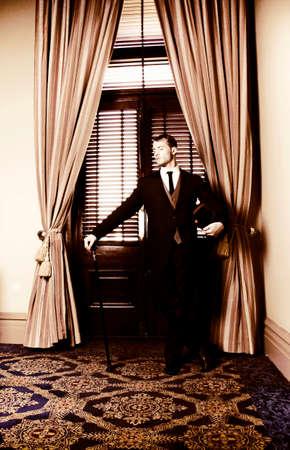 sirvientes: sirviente retro haciendo guardia en la puerta de entrada con cortinas que sostiene el bastón y el sombrero de copa maestros mientras espera pacientemente para ser de servicio