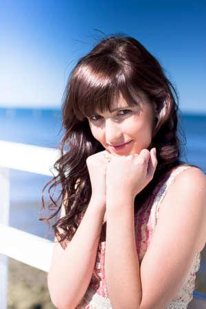 mujer sola: Retrato de medio cuerpo atractivo de la mujer joven en una playa de vacaciones descansando la cabeza sobre las manos mar azul y el cielo en el fondo