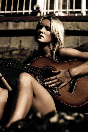 sentimental: Beautiful Dark Portrait Of A Sexy Sentimental Female Musician Performing And Singing A Song While Strumming On A Guitar At Midnight Stock Photo