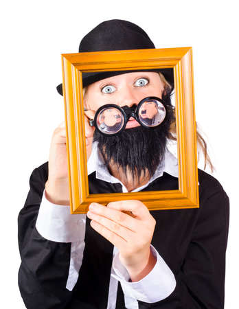 travesty: Artistic man looking through empty picture frame. Artwork valuation concept
