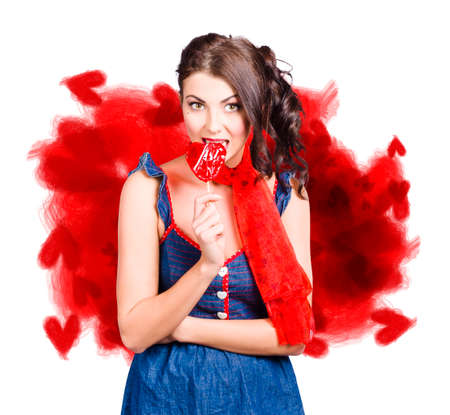 woman in love: Young beautiful valentines day woman eating heart candy on love heart gift card background