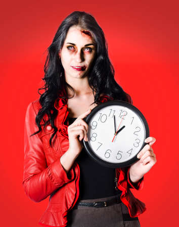 gruesome: Creepy business woman holding a clock when under deadly time pressure from a halloween DEADline