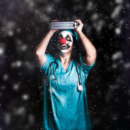 raining: Doctor loco payaso de pie en la lluvia que cae con botiquín de primeros auxilios. Broma crisis Salud Foto de archivo